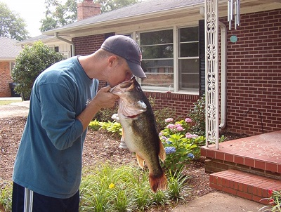 man looking into fish mouth