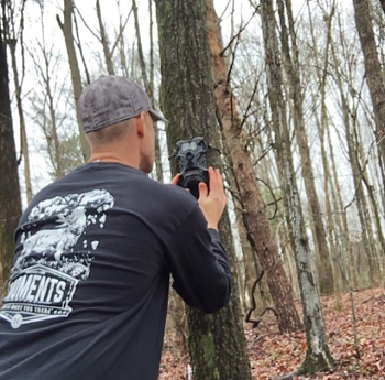 man mounting a trail camera to a tree