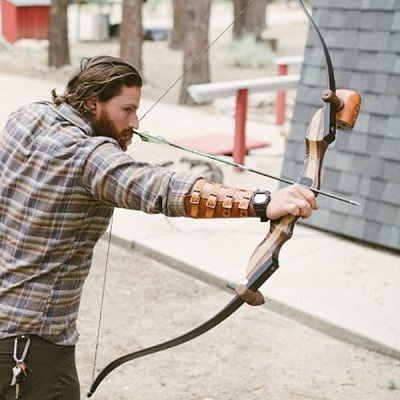 man holding recurve bow at full draw