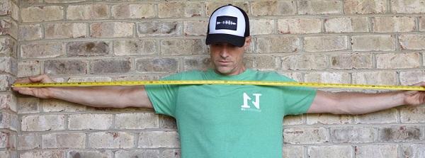 man measuring armspan for bowhunting