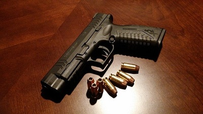 pistol with bullets on table