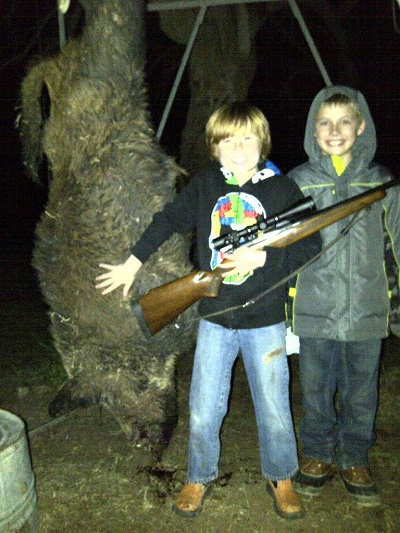 kids holding rifle standing next to dead hog